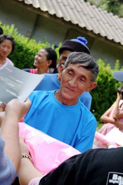Elderly man receiving a mosquito net